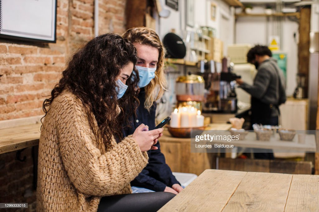 happy couple in love with face mask in coffe shop : Stock Photo
