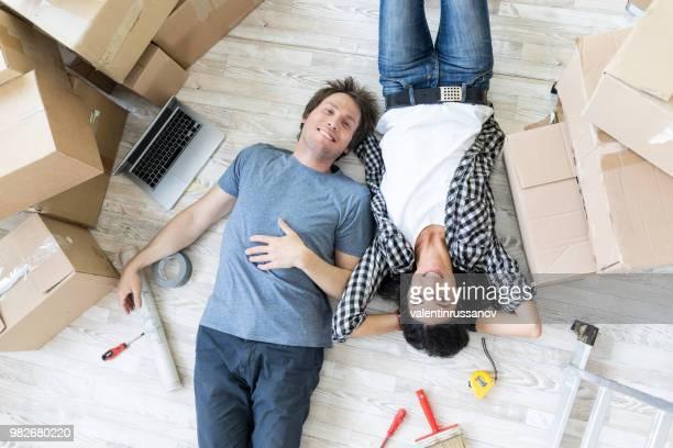 couple heureux dans une maison neuve, couché - demenagement humour photos et images de collection