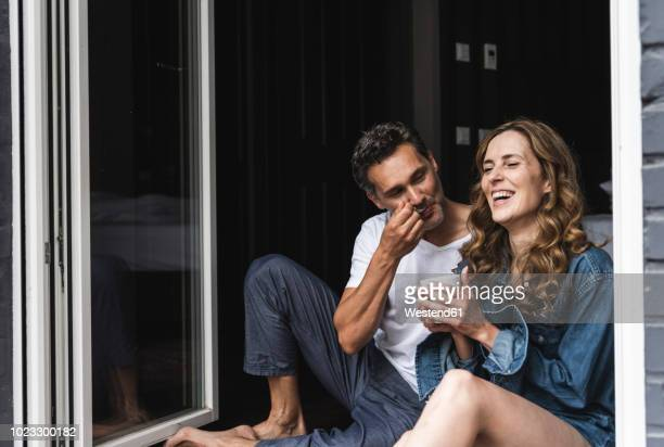 happy couple in nightwear at home sitting at french window - koppel stockfoto's en -beelden