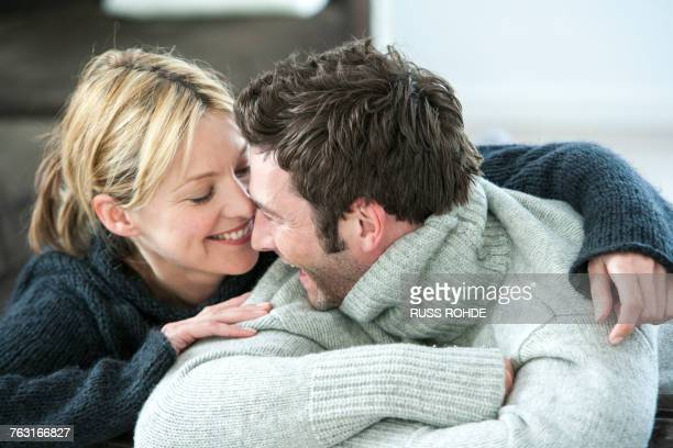 Happy couple in polo neck sweaters gazing at each other