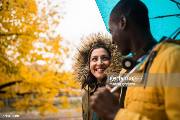 happy couple in rain - multi colored coat stock photos and pictures