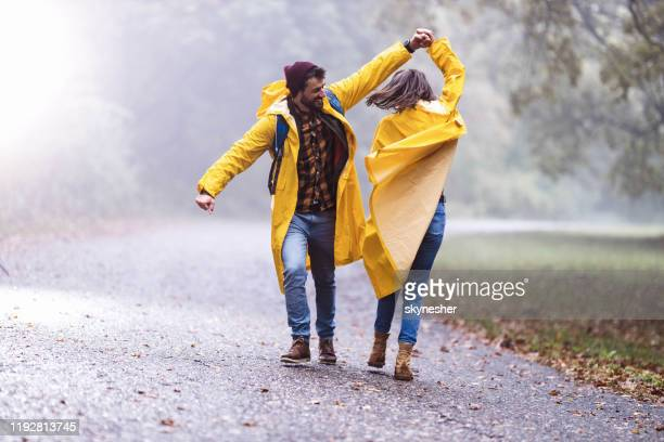 happy couple in raincoats having fun while dancing on a rain in misty forest. - rain stock pictures, royalty-free photos & images