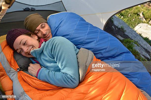 Happy couple in sleeping bags in tent at Fault Lake, Selkirk Mountains, Idaho
