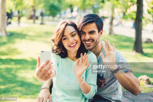 happy couple in the city park enjoying a video call - long distance relationship stock pictures, royalty-free photos & images