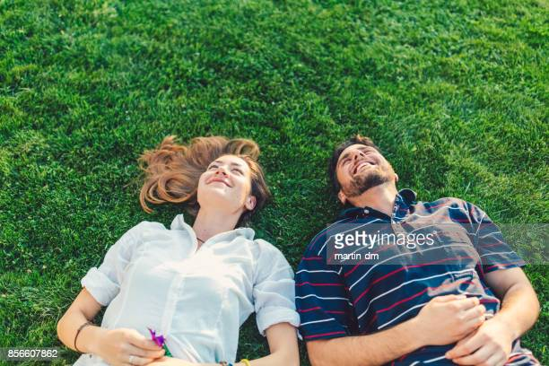 happy couple in the grass dreaming - lying down foto e immagini stock
