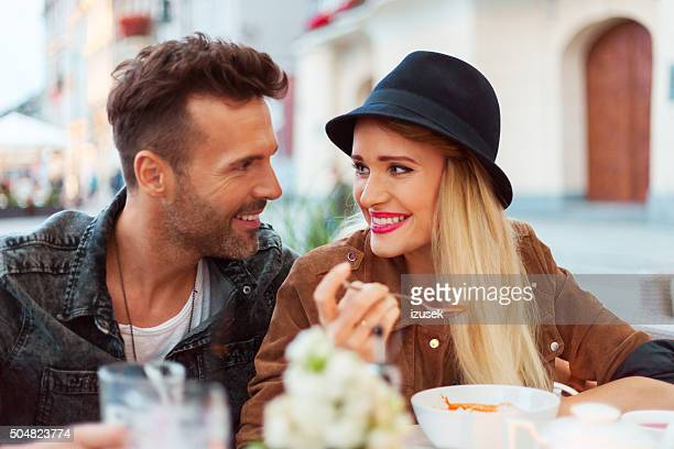 Happy couple in the outdoor restaurant, woman eating soup