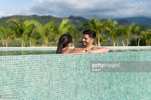 Happy couple in the pool enjoying their summer vacations