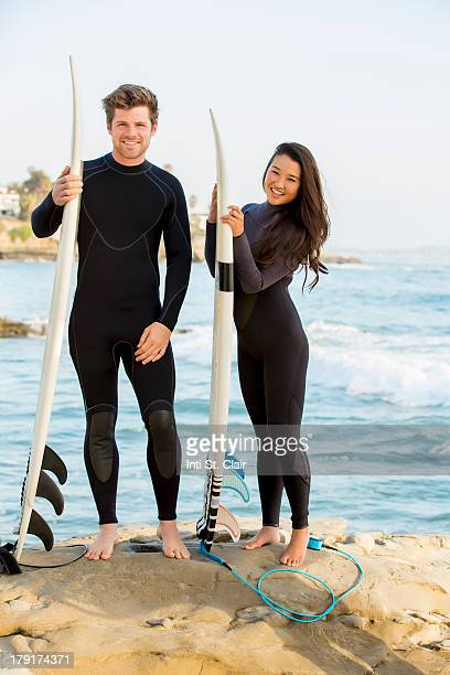 Happy couple in wetsuits with surfboards at beach