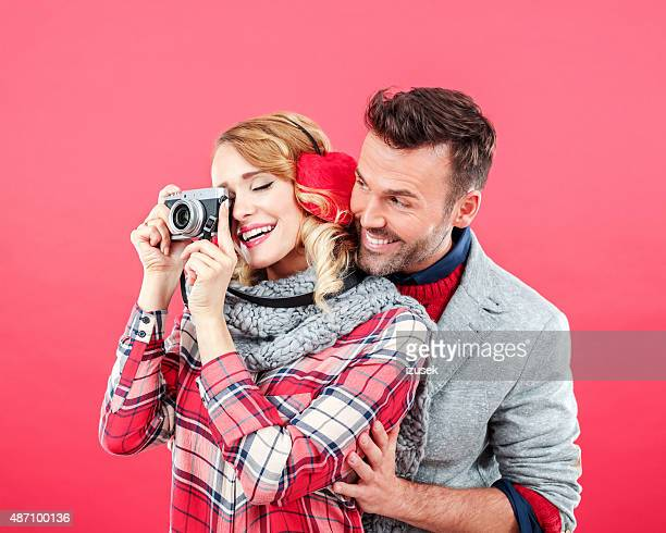 happy couple in winter outfit against red background - izusek stock pictures, royalty-free photos & images