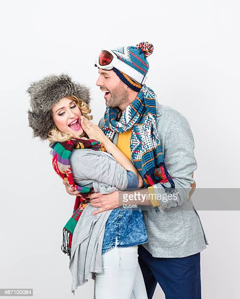 happy couple in winter outfit against white background - izusek stock pictures, royalty-free photos & images