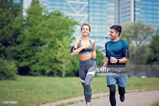 happy couple is running in a city - arm band stock pictures, royalty-free photos & images