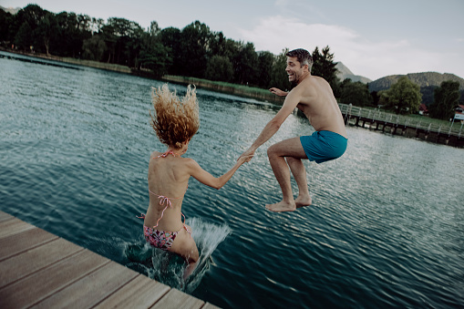 Happy couple jumping hand in hand into swimming lake - gettyimageskorea