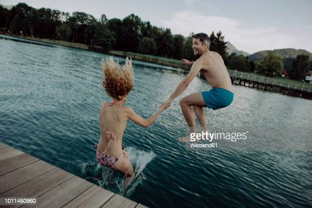 happy couple jumping hand in hand into swimming lake - see stock-fotos und bilder