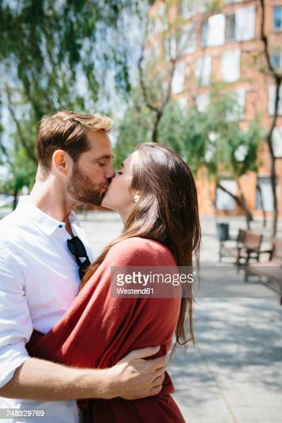 happy couple kissing and hugging in the street - mid adult men foto e immagini stock
