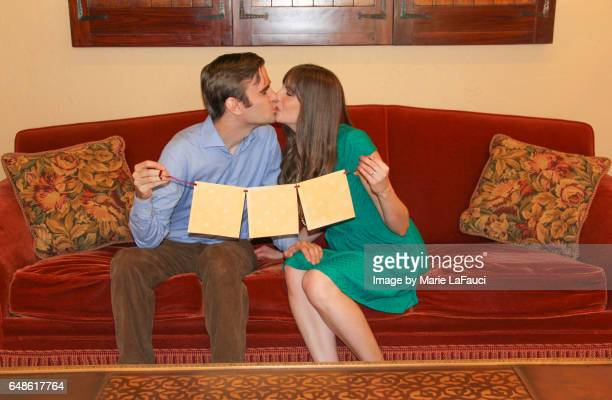 Happy couple kissing on sofa holding a sign