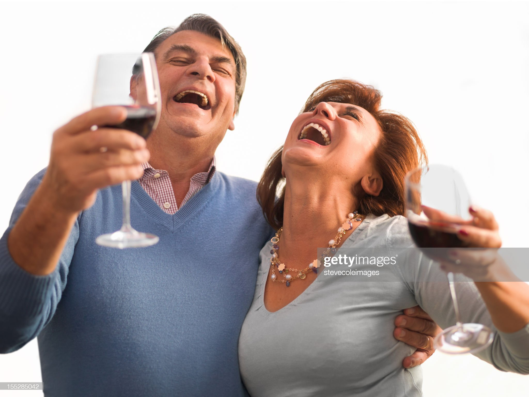 happy-couple-laughing-holding-wine-glass