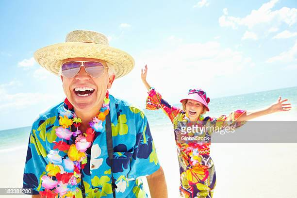 happy couple laughing in the sun - multi colored hat stock pictures, royalty-free photos & images