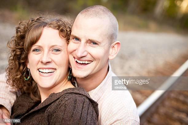 coppia felice ridendo insieme fuori per ferrovia - abbracciarsi a letto foto e immagini stock