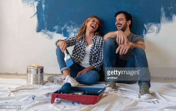 glückliches paar lacht beim malen ihres hauses - malen stock-fotos und bilder