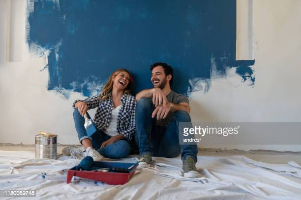 happy couple laughing while taking a break from painting - dipinto foto e immagini stock