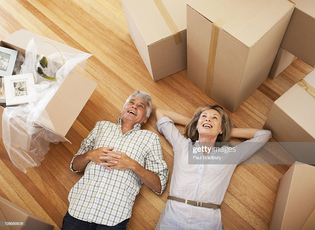 Happy couple laying on floor of new house : Stock Photo