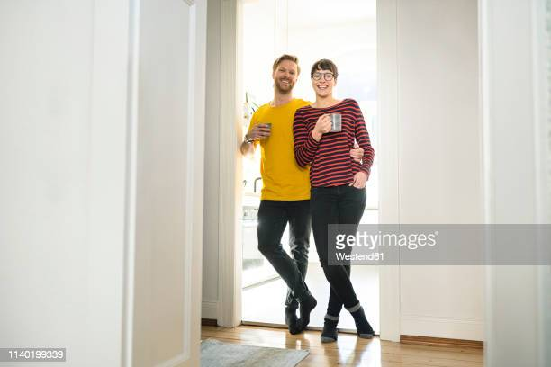 happy couple leaning in door case in front of their kitchen - 35 39 anni foto e immagini stock