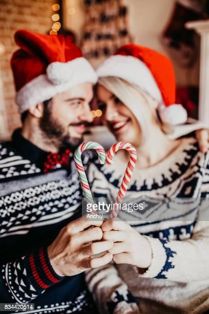Glückliches Paar sahen einander und machen Herzform aus Weihnachten Zuckerstange
