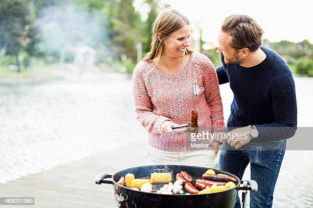 Happy couple looking at each other while barbecuing on pier