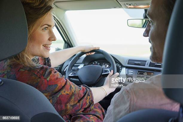 Happy couple looking at each other while traveling in car
