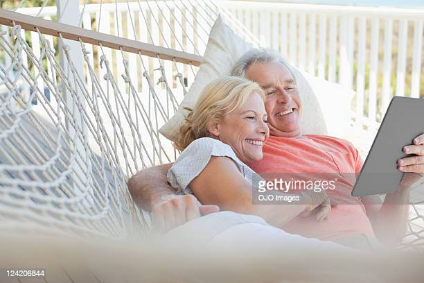 happy couple looking at electronic book in hammock - hammock stock pictures, royalty-free photos & images