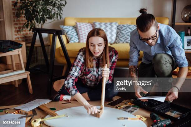 Happy couple looking at instructions to assemble new coffee table