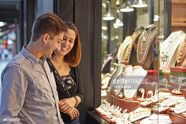 Happy couple looking at jewelry shop window
