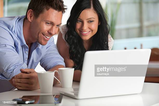 Happy couple looking at laptop computer