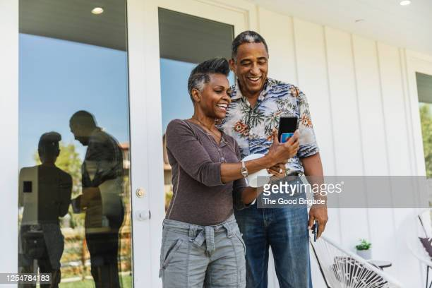 happy couple looking at smart phone - mature men stock pictures, royalty-free photos & images