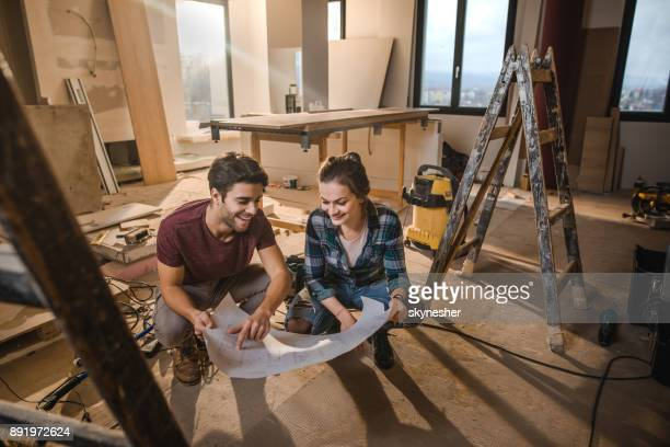 happy couple looking at their housing project on construction site. - reform stock pictures, royalty-free photos & images