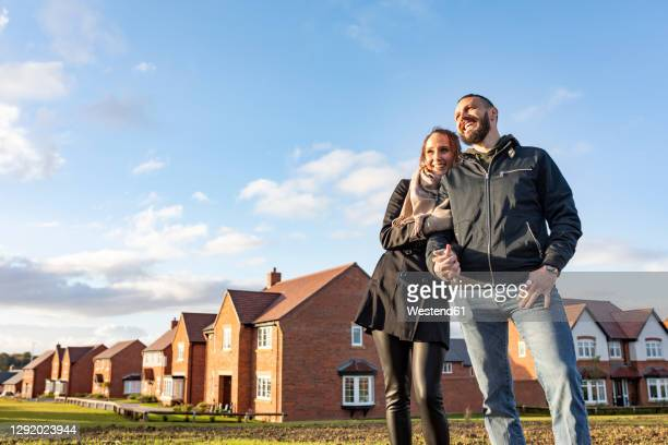 happy couple looking away while standing outside newly built houses against sky - couple relationship stock pictures, royalty-free photos & images