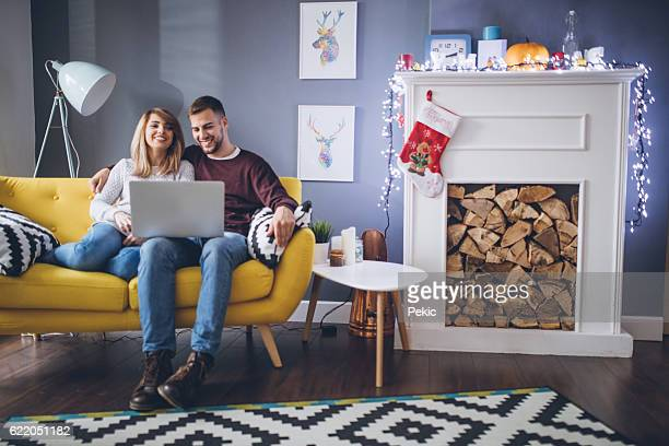 Happy couple looking funny videos on their laptop