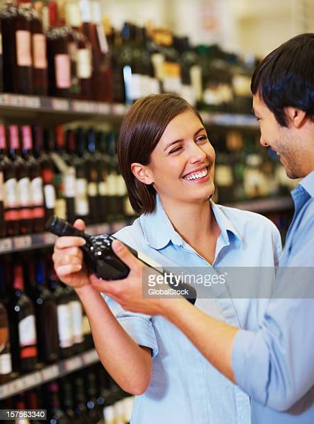 Happy couple looking out for a wine bottle