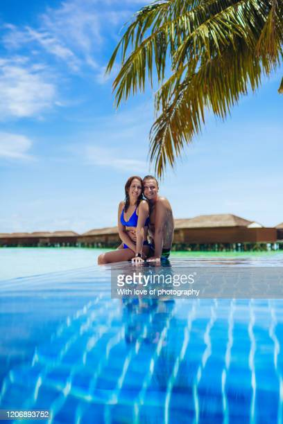 happy couple lovers relaxing embracing in infinity pool on the beach in maldives, luxury vacation, young adult man and woman on tourist resor by the ocean, island vibes, summer vacation, relaxing and embracing - love island stock pictures, royalty-free photos & images