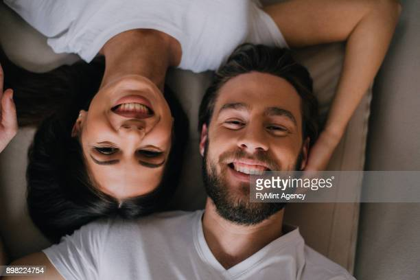 Happy couple lying cheek to cheek in a bed.