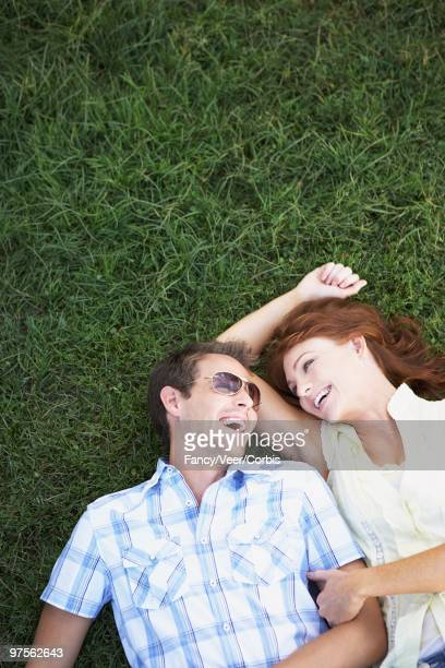 happy couple lying down in the grass - down blouse stock pictures, royalty-free photos & images