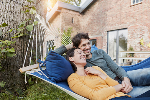 Happy couple lying in hammock in garden of their home - gettyimageskorea