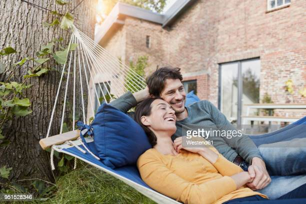 happy couple lying in hammock in garden of their home - mid volwassen stockfoto's en -beelden