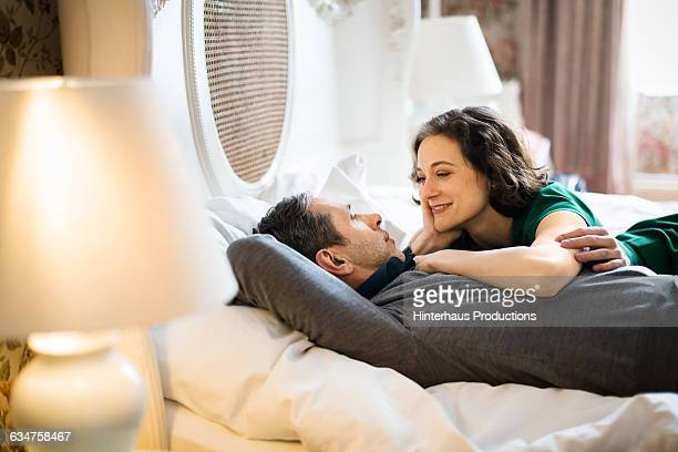 A happy couple lying on a big hotel bed.