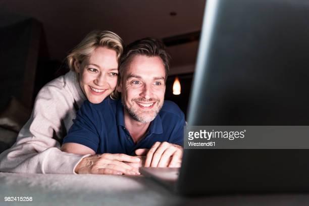 happy couple lying on couch at home looking at laptop - op de buik liggen stockfoto's en -beelden