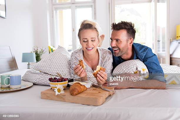 Happy couple lying on the bed, eating breakfast