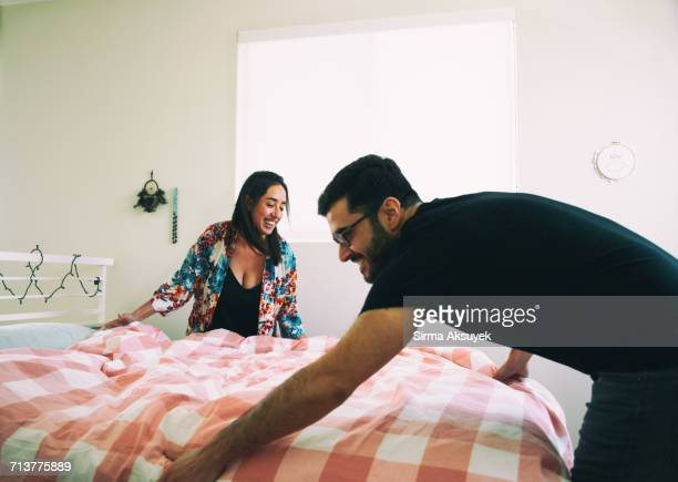 Happy couple making bed together