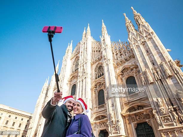 Feliz pareja haciendo autofoto frente a la Catedral Duomo de Milán
