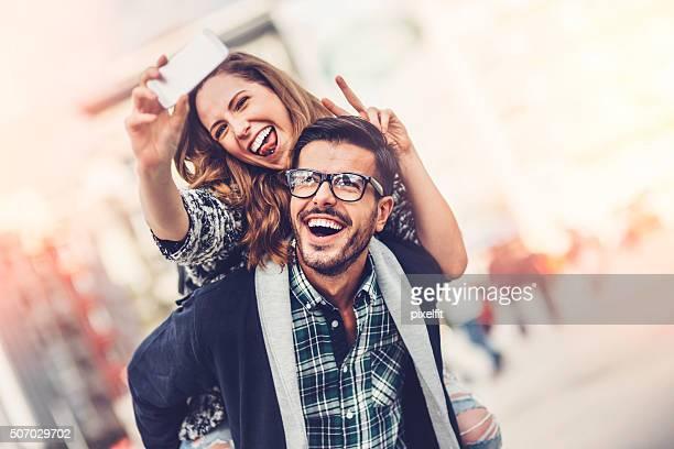 happy couple making selfie outdoors - vriendje stockfoto's en -beelden
