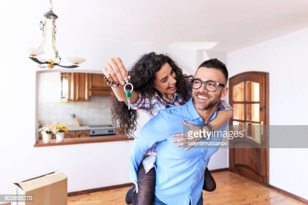 happy couple moving in new home - house key stock photos and pictures